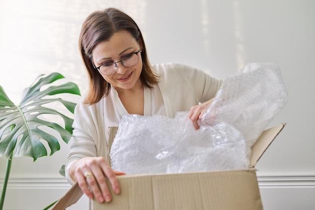 Зрелая женщина распаковывает картонную коробку на столе дома, в офисе