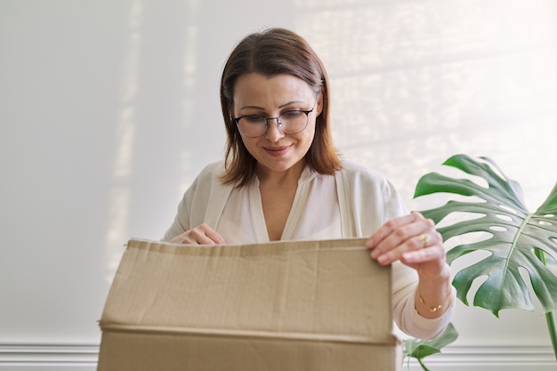 Mature woman unpacks cardboard box on table at home, in office. service for international postal delivery, auto delivery of goods, cargo. female received purchases purchased in online stores