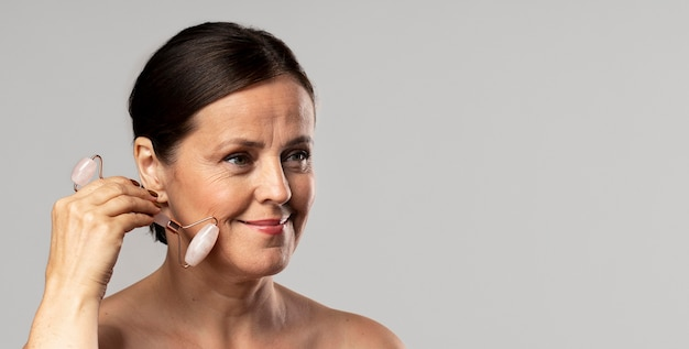Mature woman using rose quartz face roller with copy space