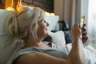 Mature woman using smartphone on bed