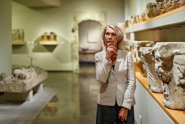 Зрелая женщина, посещающая художественный музей
