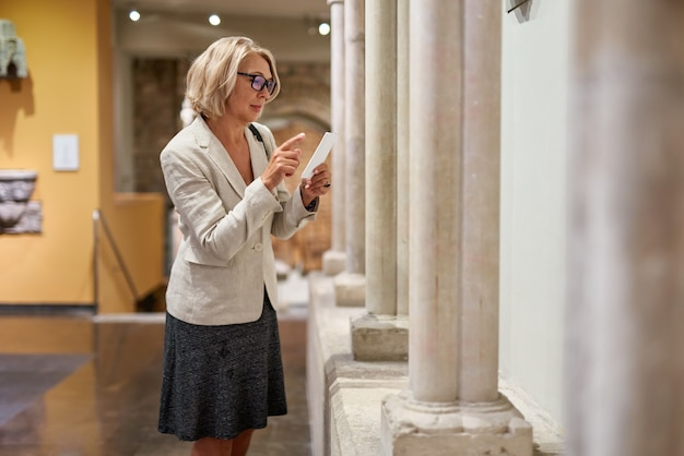 Mature woman visitor near columns in the historical museum