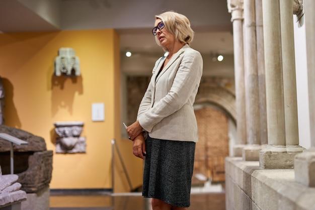 歴史博物館の柱の近くにいる熟女の訪問者