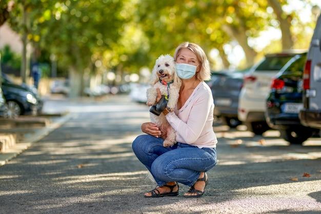 Зрелая женщина гуляет с собакой на открытом воздухе в антивирусной маске