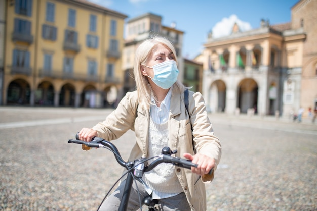 Mature woman wearing face medical mask while riding a bicycle during covid pandemic outdoors