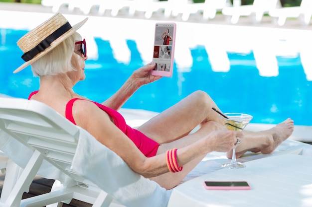 Mature woman wearing red swimming suit watching photos on laptop while sunbathing