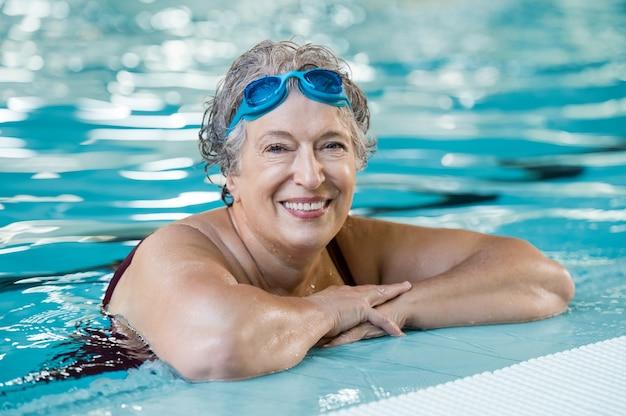 スイミングプールで水泳ゴーグルを身に着けている成熟した女性