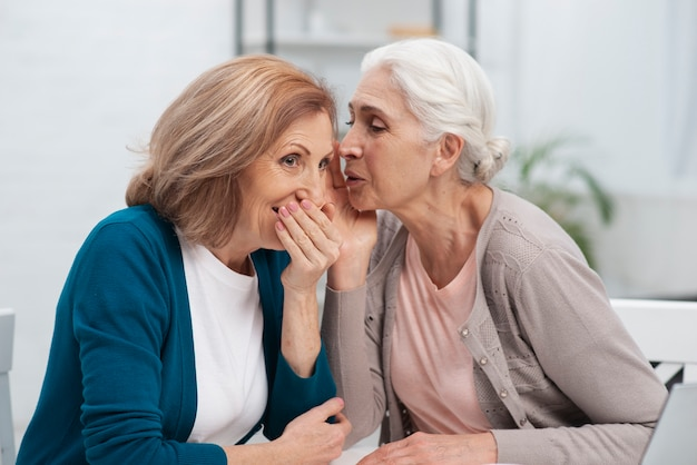Mature woman whispering to her friend