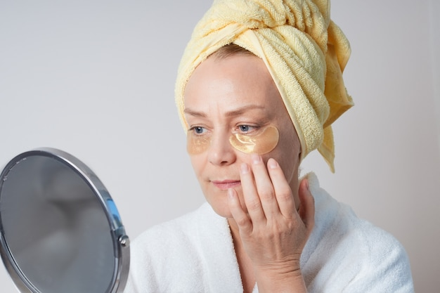 A mature woman in a white morning robe, with a yellow towel on her head, applying patches under her eyes, looking in the mirror.