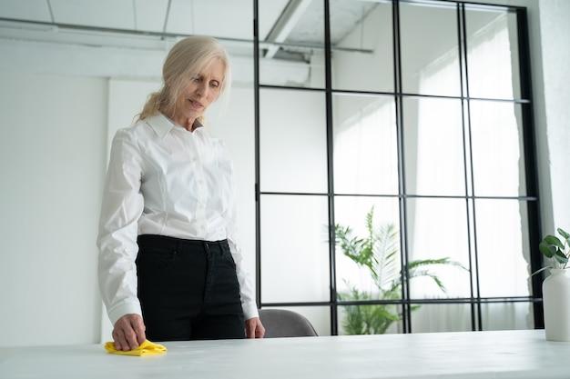 Пожилая женщина протирает деревянный стол тряпкой, пожилая женщина улыбается и вытирает пыль