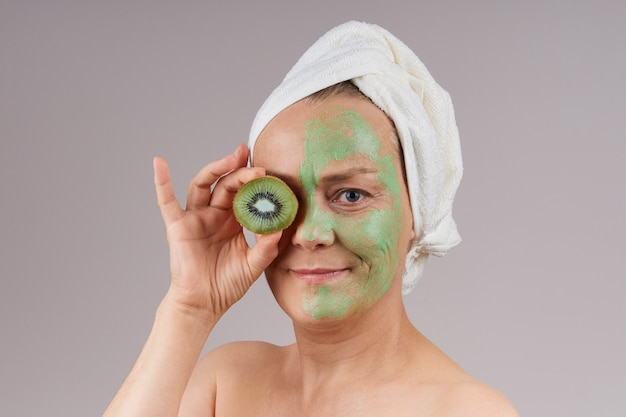 Mature woman with bare shoulders, white towel on her head, applied green fruit mask on her face, kiwi closed her eyes. facial skin care concept.  over gray wall.