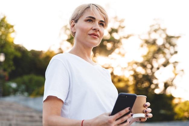街の階段に立っている間、携帯電話とコーヒーと紙コップを保持しているカジュアルな服を着ているブロンドの髪の成熟した女性