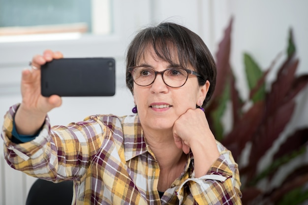 Mature woman with checked shirt making selfie