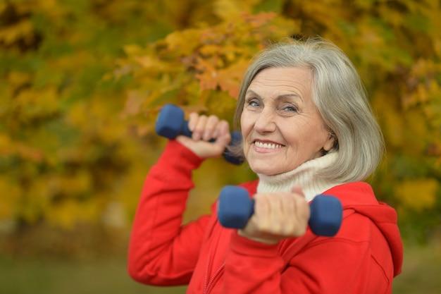 秋の公園でダンベルを持つ成熟した女性