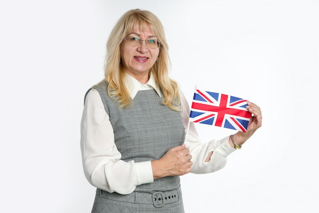 Mature woman with flag of great britain on bright background.