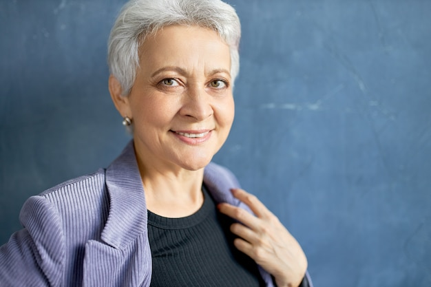 Mature woman with grey hair posing with violet jacket