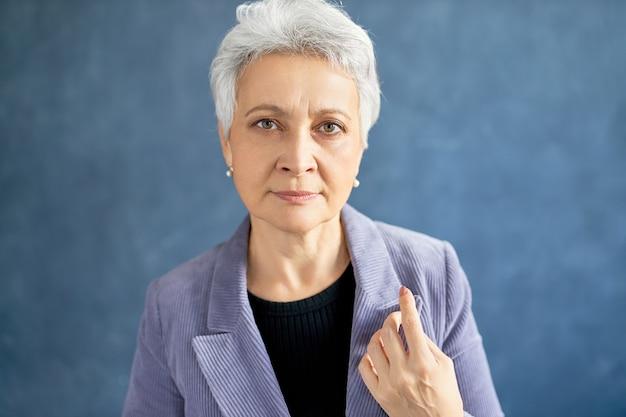 Зрелая женщина с седыми волосами позирует в фиолетовой куртке