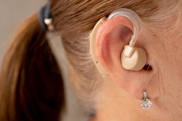 Пожилая женщина со слуховым аппаратом.