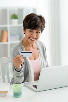 Зрелая женщина с ноутбуком и кредитной тележкой