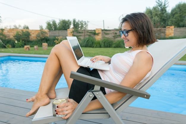 プライベートホームプールの近くにラップトップを持つ成熟した女性