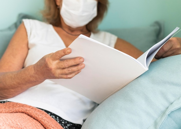 Mature woman with medical mask at home during the pandemic reading a book
