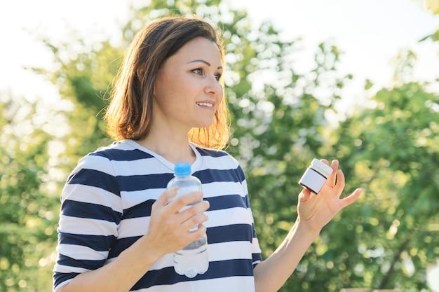 薬、ビタミン、サプリメントの薬瓶を持つ成熟した女性