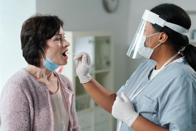 Зрелая женщина с открытым ртом сидит перед врачом в перчатке, проверяет ее на covid с помощью мазка из полости рта в медицинском кабинете современных клиник