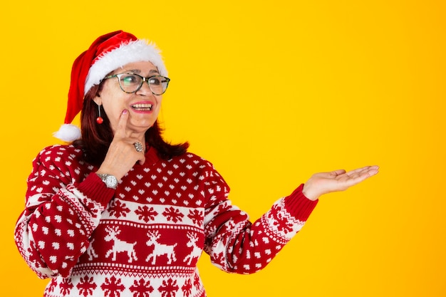 Mature woman with santa claus hat happy pointing copy space yellow background
