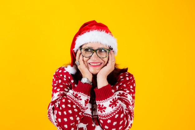 Mature woman with santa claus hat happy with his hands resting on his face