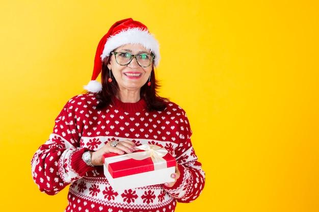 サンタクロースの帽子をかぶった成熟した女性は、クリスマスプレゼント、黄色の背景を開きます