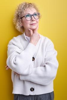 Зрелая женщина с серьезным и сконцентрированным уверенным взглядом, мозговой штурм и размышления о сложной проблеме, позирует изолированно на желтом, в элегантной одежде и очках
