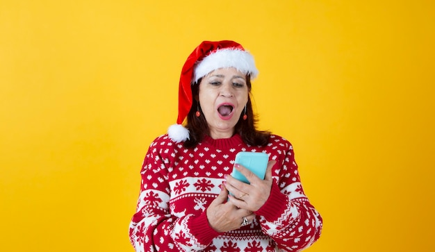 Mature woman with smartphone christmas yellow background
