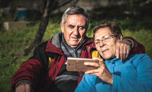 Mature woman with smartphone embraced by her husband while both sitting in park.