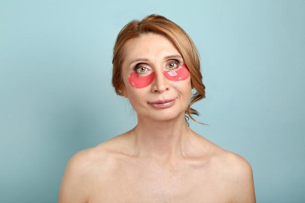 色の背景に目の下のパッチを持つ成熟した女性