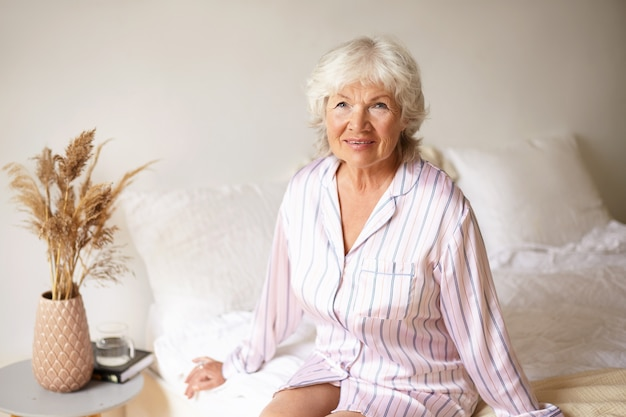 Mature woman with wrinkled skin and gray hair relaxing in bedroom, sitting on bed in silk night gown, looking with charming joyful smile, book, glass of water and dry plant on bedside table