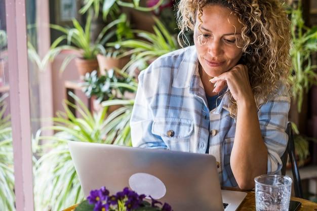 Зрелая женщина работает за компьютером, сидя на рабочем столе домашнего офиса и улыбаясь, глядя на ноутбук - бесплатные современные люди-фрилансеры - умная работа в интернете, работа в интернете, образ жизни - общение