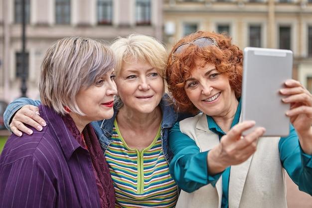 중년 여성들이 태블릿 pc로 밖에서 사진을 찍고 있습니다.