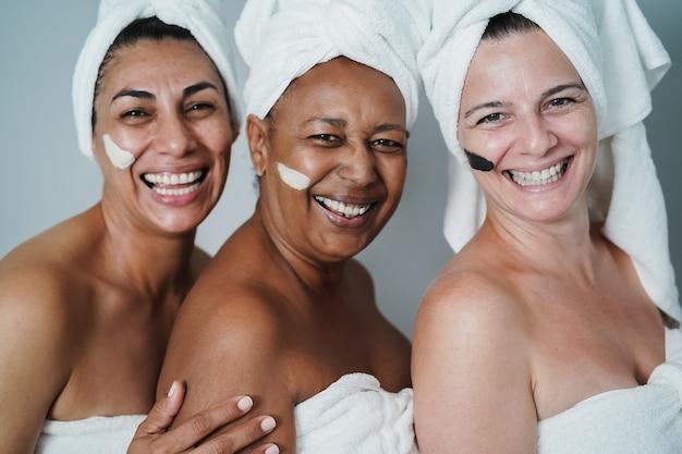 피부 마스크를 사용하여 스파에서 미용 치료를 하면서 함께 웃고 있는 성숙한 여성 - 아프리카 여성의 얼굴에 대한 주요 초점 - 오른쪽 집의 얼굴에 대한 주요 초점