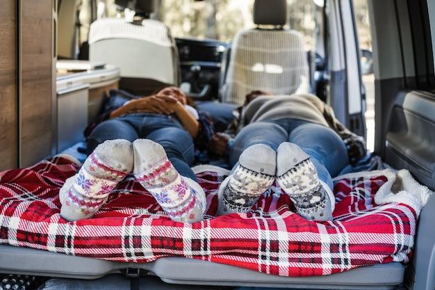 Mature women sleeping inside mini van camper wearing christmas warm socks - focus on feet