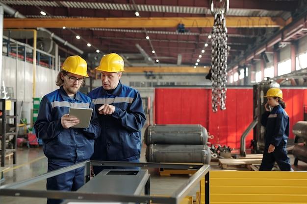 태블릿을 가리키고 금속 큐브 프레임에 서 있는 동안 동료와 생산 문제를 논의하는 안전모를 쓴 성숙한 작업자