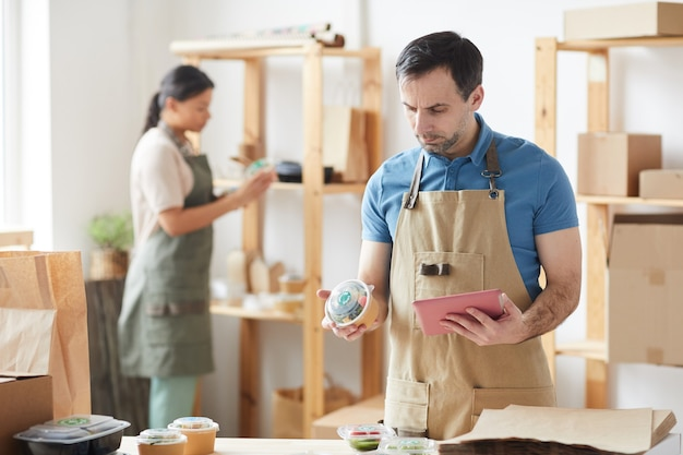 Mature worker wearing apron packaging orders while standing by wooden table, food delivery service