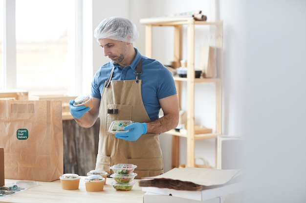 Mature worker wearing protective clothes safely packaging orders at wooden table in food delivery service