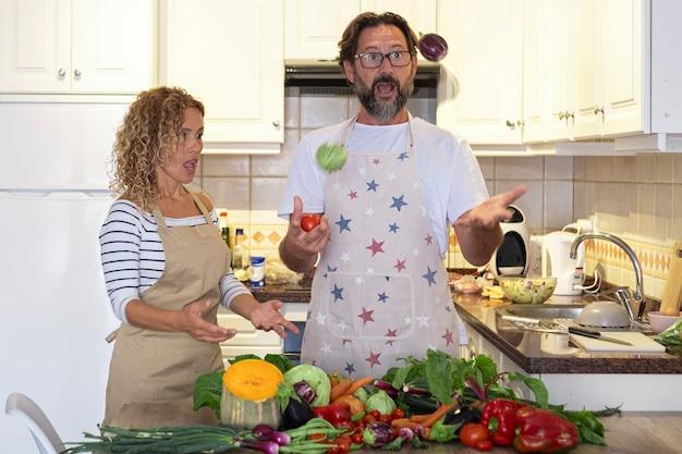 成熟した若い大人の男性と女性は、新鮮な野菜と一緒に昼食の準備中にキッチンで遊んで楽しんでいます。幸せなカップルは家で一緒に時間を楽しんでいます
