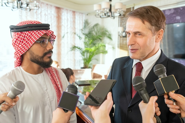 Mature and young male delegates standing in front of journalists with microphones and answering their questions during interview