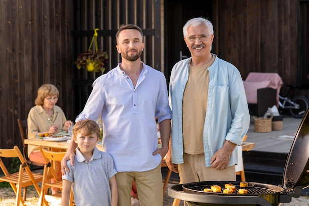 Mature and young men and cute boy standig by grill in front of camera