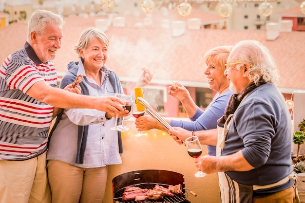 Matures group of elderly people enjoying together a barbecue at home laughing and smiling - happy active retired senior lifestyle - friendship and celebration concept - city view