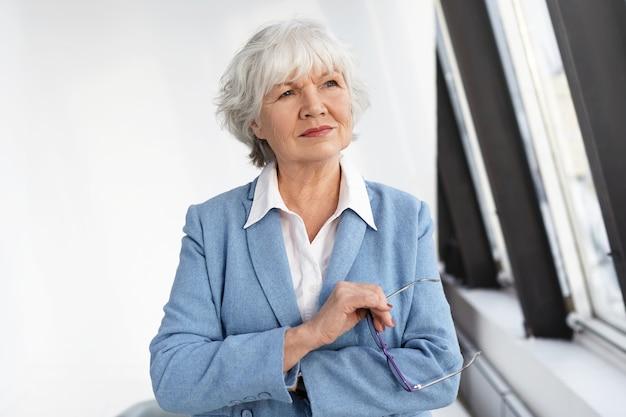 성숙, 고령화 및 고용 개념. 매력적인 경험이 풍부한 성숙한 여성 기업가 흰색 셔츠 위에 우아한 파란색 재킷을 입고 그녀의 사무실에서 숙고하고 안경을 들고 웃고