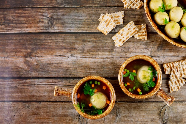 Matzo ball soup in two plates with spoons on wooden background.