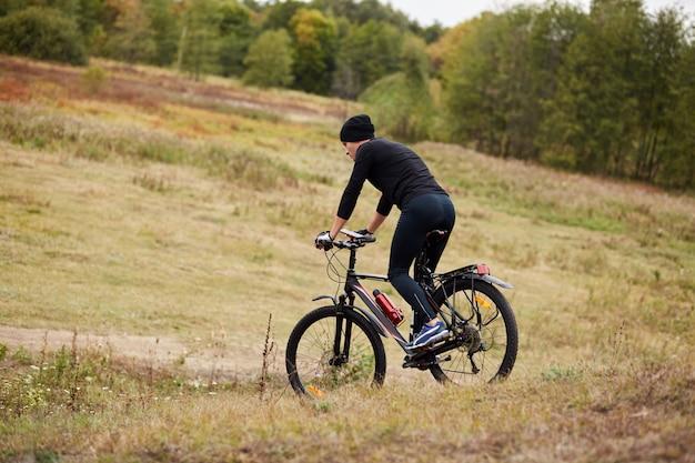 Изображение велосипедиста mauntain на лугу возле леса, вид сбоку спортивный мужской велосипед во время отпуска