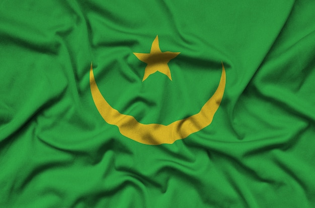 Mauritania flag  is depicted on a sports cloth fabric with many folds.